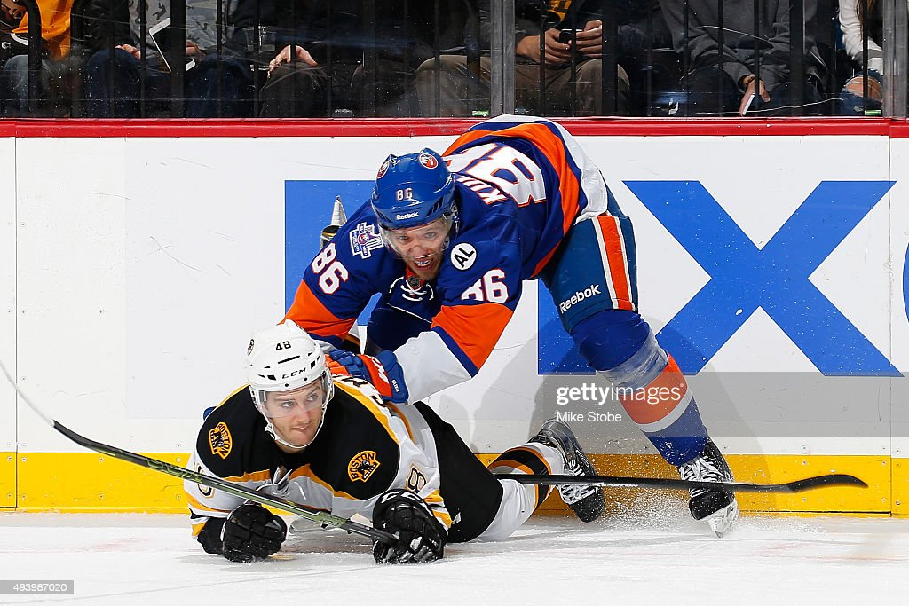 Nikolay Kulemin #86 of the New York Islanders gets tangled up on the ice with Colin Miller #48 of the Boston Bruins at the Barclays Center on October 23, 2015 in Brooklyn borough of New York City. The Bruins defeated the Islanders 5-3.