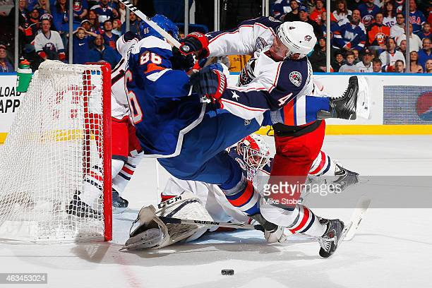 Nikolay Kulemin of the New York Islanders is checked in front of the goal by Kevin Connauton of the Columbus Blue Jackets at Nassau Veterans Memorial...