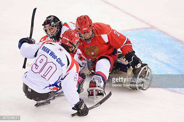 Nikolay Terenyev of Russia crashes into ManGyun Yu of Korea during the Ice Sledge Hockey Preliminary Round Group A match between the Russia and Korea...