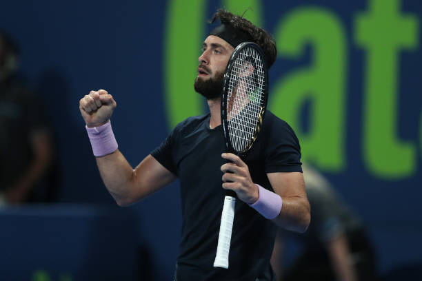 Nikoloz Basilashvili of Georgia celebrates victory in his quarter final match with Roger Federer of Switzerland in the Qatar ExxonMobil Open at...