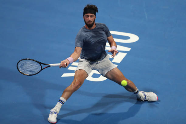 Nikoloz Basilashvili of Georgia plays a forehand during his quarter final match with Roger Federer of Switzerland in the Qatar ExxonMobil Open at...