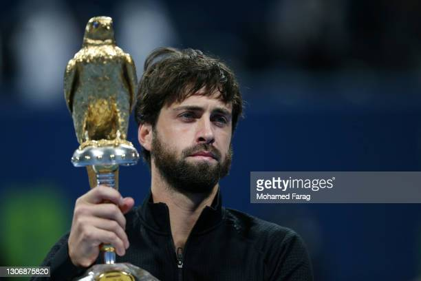 Nikoloz Basilashvili of Georgia poses with the trophy following victory in The Qatar ExxonMobil final between Roberto Bautista Agut and Nikoloz...
