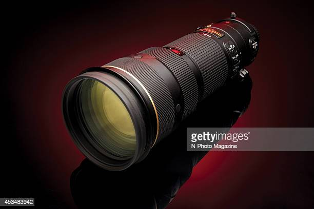 A Nikon AFS 200400mm f/4G ED VR II telephoto lens photographed on a red background taken on November 18 2013