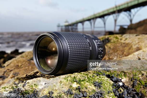 A Nikon AFS 70300mm f/4556G ED VR camera lens on seaweedcovered rocks at Clevedon beach with Clevedon pier visible in the background taken on January...