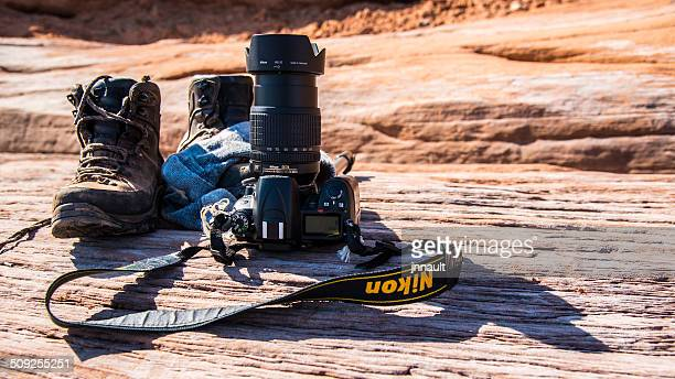 nikon camera with boots on the ground after a hike. - nikon stock pictures, royalty-free photos & images