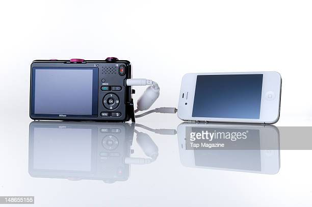 A Nikon Coolpix S1200PJ digital camera and projector attached to an Apple iPhone 4 taken on October 28 2011