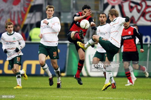 Nikos Liberopoulos of Frankfurt is challenged by Aaron Hunt of Bremen during the Bundesliga match between Eintracht Frankfurt and Werder Bremen at...