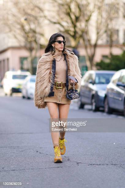 Nil Ninat wears sunglasses, earrings, a necklace, a beige turtleneck, a beige fur jacket, a brown belt, a camel corduroy mini skirt, a small studded...