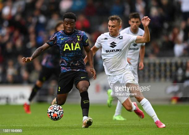 Nile John of Tottenham Hotspur is challenged by Scott Twine of Milton Keynes Dons during the Pre-Season Friendly match between Milton Keynes Dons and...