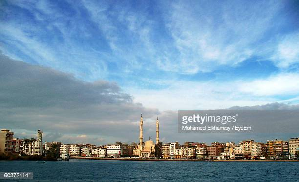 Nile River In Front Of Mosque And Buildings In City Against Cloudy Sky