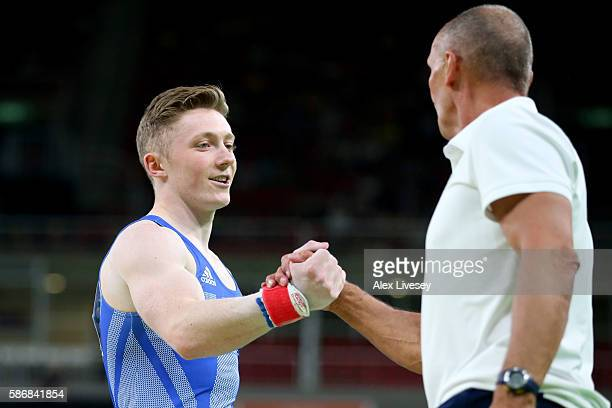 Nile Wilson of Great Britain celebrates with coach Eddie Van Hoof after competing on the pommel horse in the Artistic Gymnastics Men's Team...