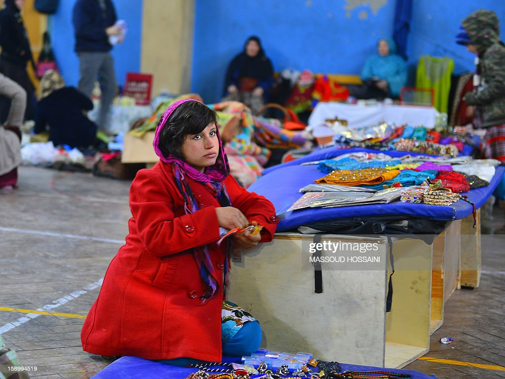 Niloofar, 16, who lost her husband and two sisters in a suicide attack, sells items during a monthly bazaar at the International Security Assistance Force (ISAF) headquarters in Kabul on January 5, 2013. Analysts have warned the country could plunge into another large-scale civil war after the NATO-led force departs by 2015. AFP PHOTO / Massoud HOSSAINI