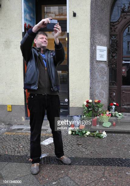 Nils Ahrens a local resident since 35 years takes photos of himself with the flowers and candles which have been placed around a photo of David Bowie...