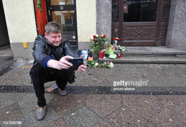 Nils Ahrens a local resident since 35 years takes photos of the flowers and candles which have been placed around a photo of David Bowie in front of...
