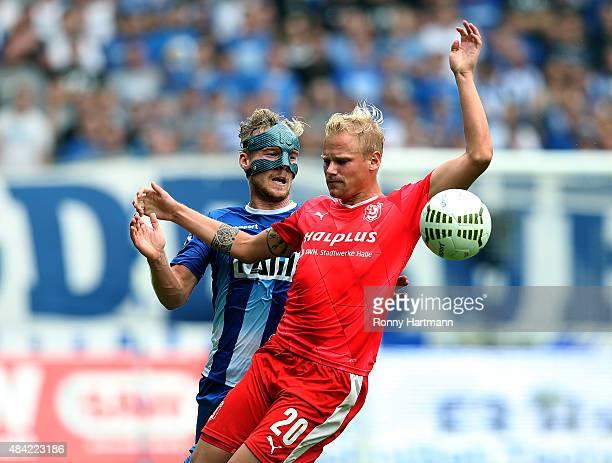 Nils Butzen of Magdeburg vies with Soeren Bertram of Halle during the Third League match between 1 FC Magdeburg and Hallescher FC at MDCCArena on...