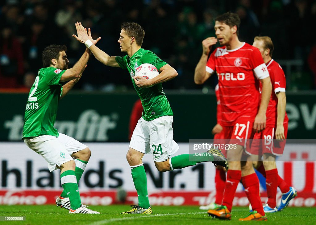 Nils Petersen (2nd L) of Bremen celebrates with his team mate Sokratis Papastathopoulos after scoring his team's first goal during the Bundesliga match between SV Werder Bremen and Fortuna Duesseldorf at Weser Stadium on November 18, 2012 in Bremen, Germany.