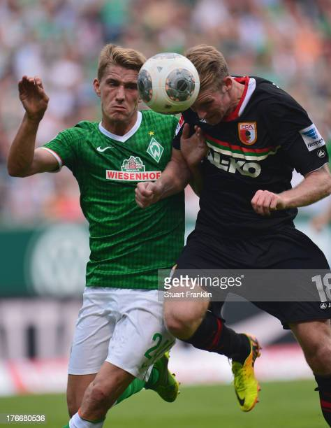 Nils Petersen of Bremen is challenged by Jan-Ingwer Callsen-Bracker of Augsburg during the Bundesliga match between Werder Bremen and FC Augsburg at...