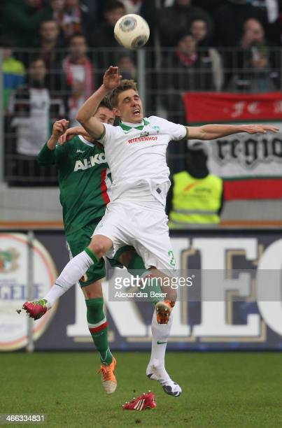 Nils Petersen of Bremen looses his football shoe as he jumps for the ball with Paul Verhaegh of Augsburg during the Bundesliga match between FC...