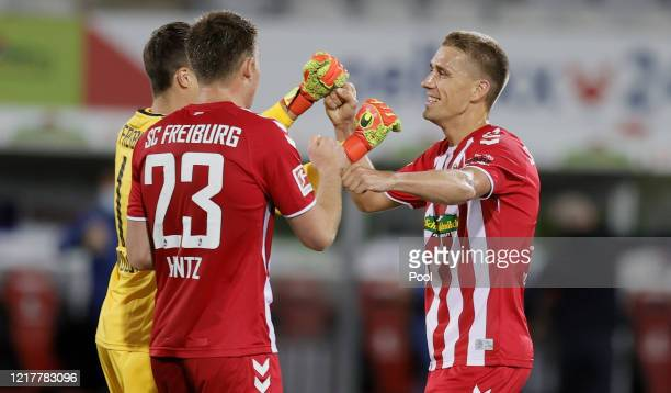 Nils Petersen of Freiburg celebrates with team mates Dominique Heintz and Alexander Schwolow following victory in the Bundesliga match between...