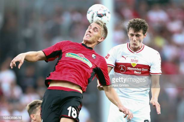 Nils Petersen of Freiburg jumps for a header with Benjamin Pavard of Stuttgart during the Bundesliga match between SportClub Freiburg and VfB...
