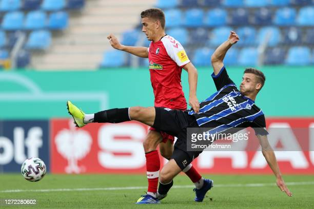 Nils Petersen of SC Freiburg is challenged by Jan Just of SV Waldhof Mannheim during the DFB Cup first round match between SV Waldhof Mannheim and...