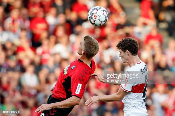 Nils Petersen of SportClub Freiburg and Benjamin Pavard of VfB Stuttgart battle for the ball during the Bundesliga match between SportClub Freiburg...