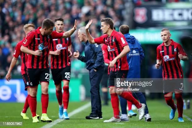 Nils Petersen of Sport-Club Freiburg celebrates with teammate Dominique Heintz after scoring his team's first goal during the Bundesliga match...