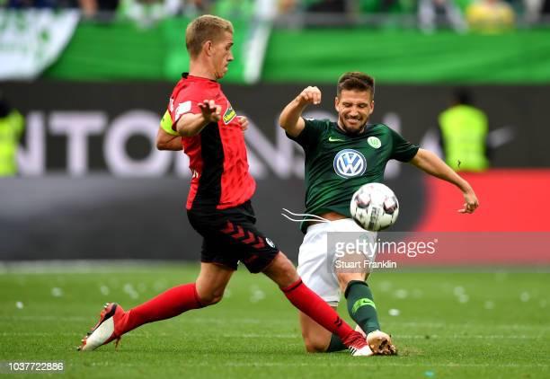 Nils Petersen of Sport-Club Freiburg is challenged by Ignacio Camacho of VfL Wolfsburg during the Bundesliga match between VfL Wolfsburg and...