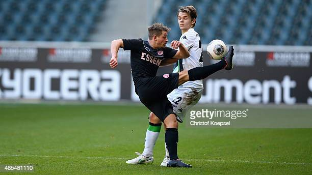 Nils Ruetten of Moenchengladbach challenges Kevin Freiberger of Essen during the Regionalliga West match between Borussia Moenchengladbach II and Rot...