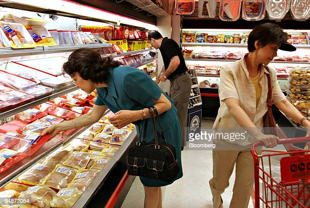 Nilsa Rosado left looks over poultry products in an Associated Supermarket in New York Wednesday June 152005 Prices paid by US consumers fell last...