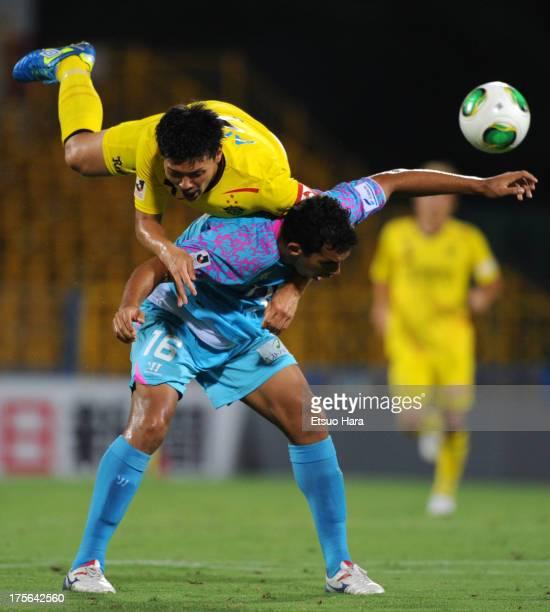 Nilson , whose real name is Ricardo da Silva Junior of Sagan Tosu and Hidekazu Otani of Kashiwa Reysol compete for the ball during the J.League match...