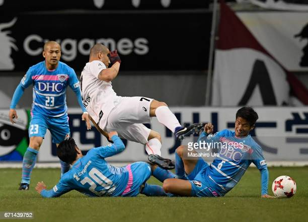 Nilton of Vissel Kobe is tackled by Yoshizumi Ogawa and Akito Fukuta of Sagan Tosu during the JLeague J1 match between Sagan Tosu and Vissel Kobe at...