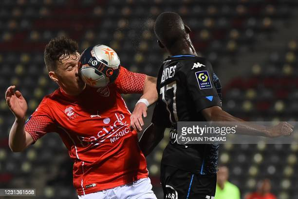 Nimes' Bosnian midfielder Haris Duljevic heads the ball with Lorient's French defender Houboulang Mendes during the French L1 football match between...