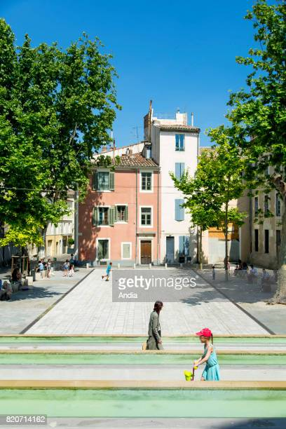 buildings in the square 'place du Chapitre ' in the town centre Building facades and atmosphere with passersby in the square