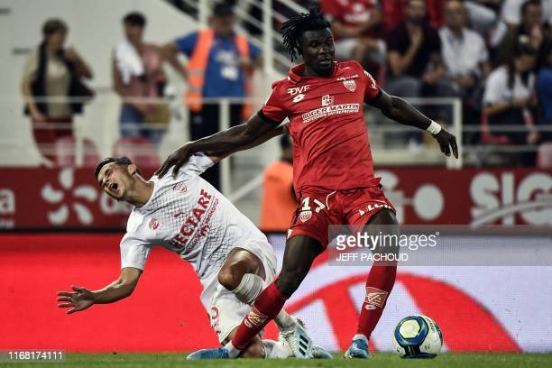 Nimes' French defender Florian Miguel vies with Dijon's Guinean defender Mama Balde during the French L1 football match Dijon vs Nimes Olympique on...