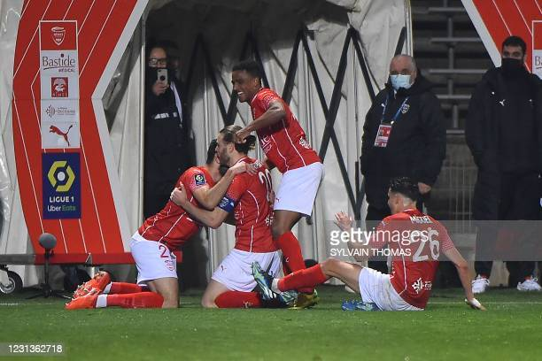 Nimes' French forward Renaud Ripart celebrates with teammates after scoring during the French L1 football match between Nimes Olympique and FC...