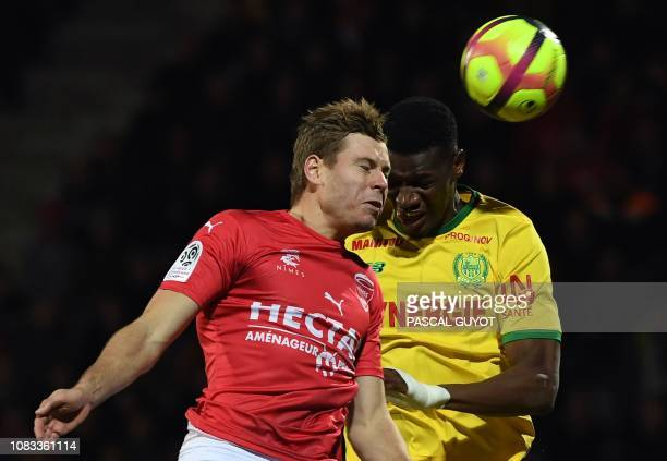Nimes' French forward Renaud Ripart vies for the ball with Nantes' Malian forward Kalifa Coulibaly during the French L1 football match between Nimes...