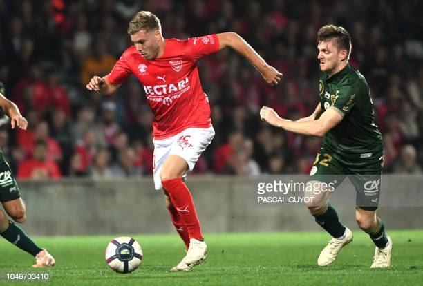 Nimes' French forward Renaud Ripart vies for the ball with Reims' Belgian defender Thomas Foket during the French L1 football match between Nimes and...