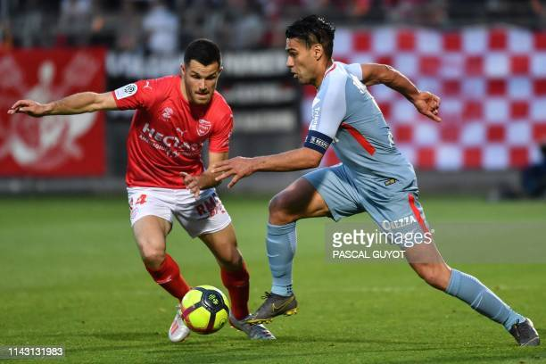 Nimes' French midfielder Antonin Bobichon fights for the ball with Monaco's Colombian forward Falcao during the French L1 football match between...