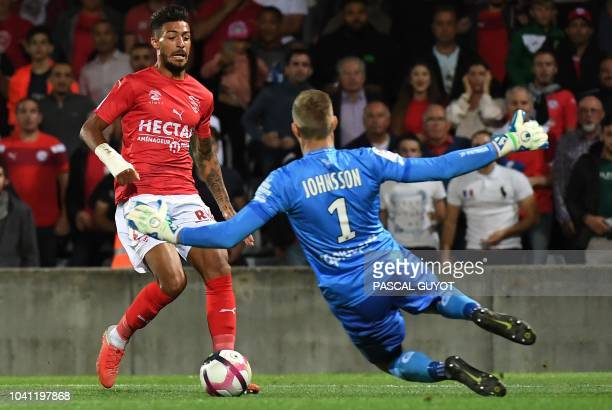 Nimes' French midfielder Denis Bouanga vies with Guingamp's Danish goalkeeper Karl-Johan Johnsson during the French L1 football match between Nîmes...