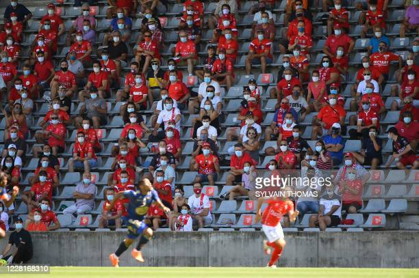 Nimes' supporters wearing protective face masks follow the French L1 football match between Nimes Olympique and Stade Brestois 29 on August 23 at the...