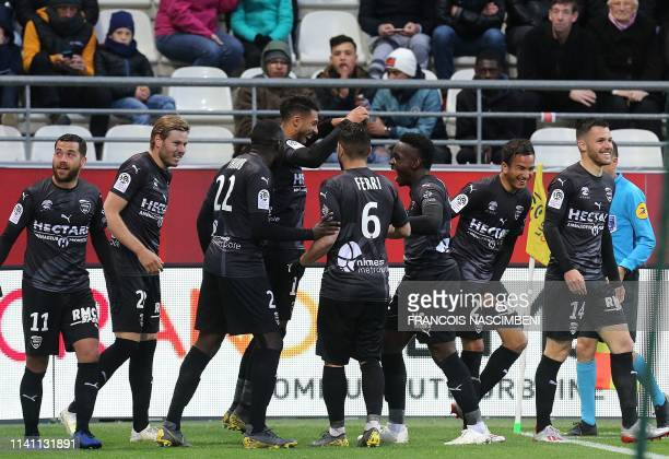 Nimes' teammates celebrate after Denis Bouanga scored during the French L1 football match between Reims And Nimes on May 4 2019 at the Auguste...
