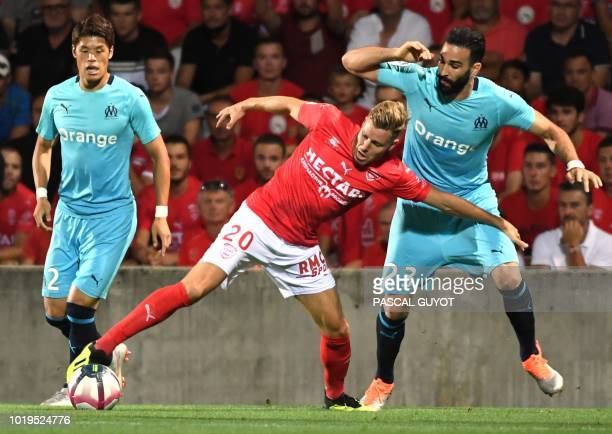 Nimes's French forward Renaud Ripart fights for the ball with Olympique Marseille's French defender Adil Rami during the French L1 football match...