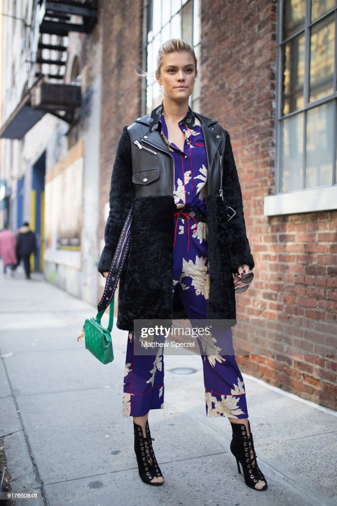 Nina Agdal is seen on the street attending Zadig & Voltaire during New York Fashion Week wearing a royal blue pattern outfit with black coat on February 12, 2018 in New York City.