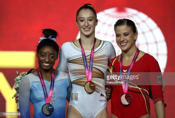 Nina Derwael of Belgium celebrates with her gold medal next to Silver medalist Simone Biles of The United States and bronze medalist Eliseabeth Seitz...