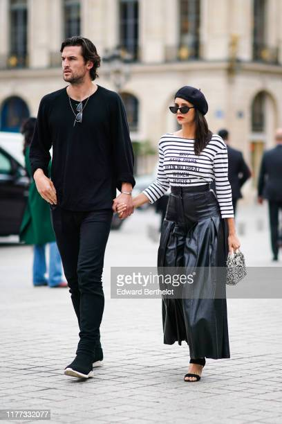 "Nina Dobrev and Grant Mellon are seen ; Nina Dobrev wears a beret hat, a black and white striped top with a printed sentence ""why have there been no..."