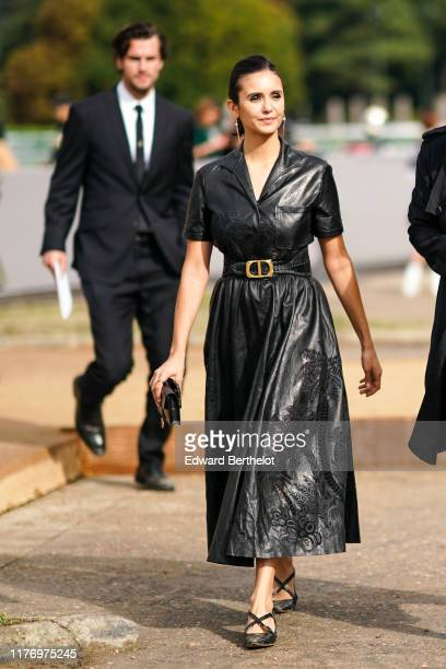 Nina Dobrev wears a black leather dress with embroidery, shoes, earrings, a belt outside Dior, during Paris Fashion Week - Womenswear Spring Summer...