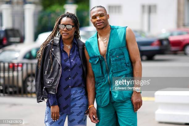 Nina Earl wears mirrored sunglasses necklaces a black leather biker jacket a navy blue shirt with the word Dance design blue pants with the word...