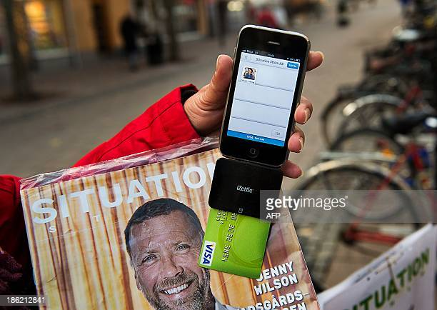 Nina Galata displays her smartphone equipped with a card reader to accept donations and payment for Situation Stockholm Stockholms homeless magazine...