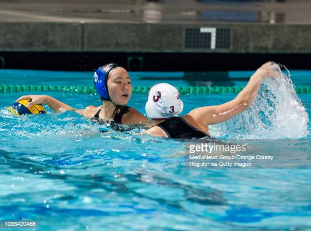 Nina Ham left of Los Alamitos looks to pass against the defense of Alana Evans of Laguna Beach during a nonleague girls water polo game at Santa Ana...